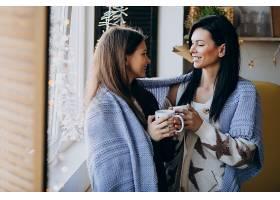 母亲和女儿在靠窗的厨房一起喝茶_6426784