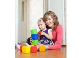 母亲和女婴在家里玩积木_1584071