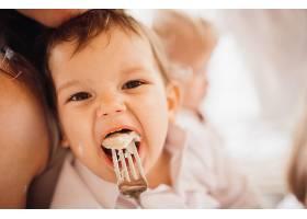 小男孩坐在父母怀里吃东西_1471675
