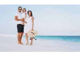 带着小女儿的年轻家庭在海边度假_5175741