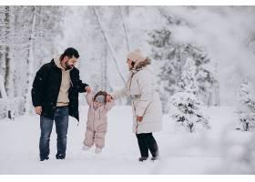 带着小女儿的年轻家庭在满是白雪的冬日森林_6641634