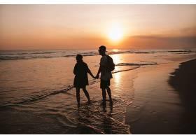 年轻浪漫情侣走在海滩上的剪影肖像女孩和_8270051