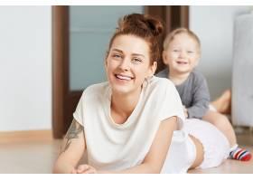 年轻的母亲和她的小儿子在家里的地板上玩耍_9660063