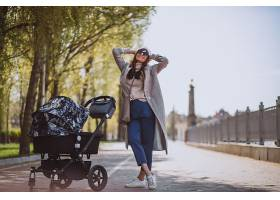 年轻的母亲推着婴儿车在公园里散步_4755308