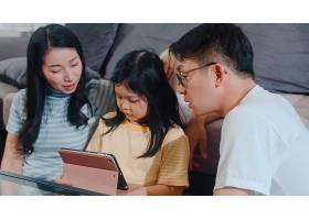 年轻的亚洲家庭和女儿在家中快乐地使用平板_6142510