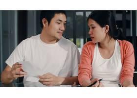 年轻的亚洲怀孕夫妇在家里记录收入和支出_6141949