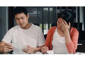 年轻的亚洲怀孕夫妇在家里记录收入和支出_6141954