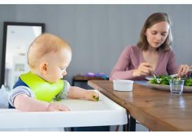 年轻的妈妈和可爱的小女儿吃着绿色蔬菜_9172449