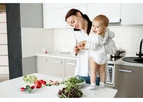 年轻的母亲一边照顾小孩一边打电话一边_9696767