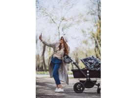 年轻的母亲推着婴儿车在公园里散步_4758580