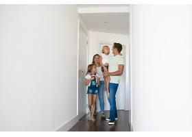 幸福的一家人穿过新房子的走廊_10608425