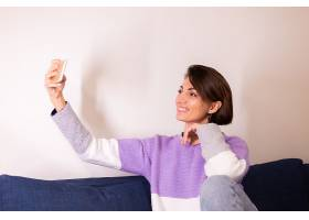 卧室里的年轻高加索女孩坐在沙发上看手机摄_13180088