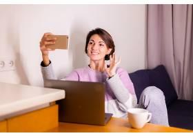 卧室里的年轻高加索女孩坐在沙发上看手机摄_13180096