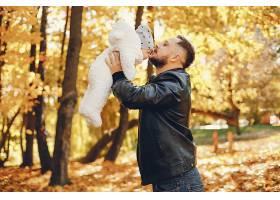 可爱的一家人在秋天的公园里玩耍_4999148