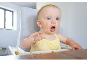 可爱的女婴脸上沾满污渍坐在高脚椅上_9649178