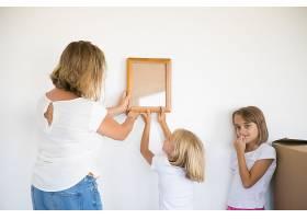 可爱的女孩在妈妈的帮助下把相框挂在白墙上_11072708