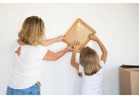 可爱的小女孩在妈妈的帮助下把相框挂在白墙_10579143