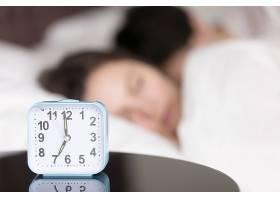 在熟睡的年轻夫妇面前的桌子上有闹钟_3955560