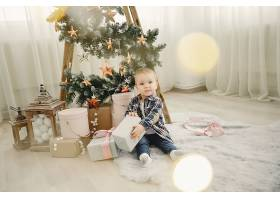 坐在圣诞树旁的可爱的一家人_3625237