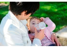女婴喝着婴儿奶瓶里的牛奶母亲用奶瓶喂女_2788674