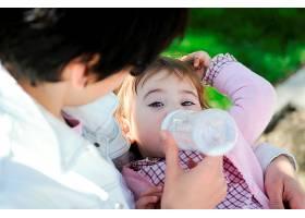女婴喝着婴儿奶瓶里的牛奶母亲用奶瓶喂女_2788675