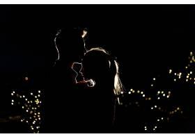 一对可爱的年轻夫妇在夜里站在屋顶上的剪影_2612655
