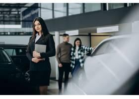 一对年轻夫妇在汽车展厅与销售人员交谈_7200764