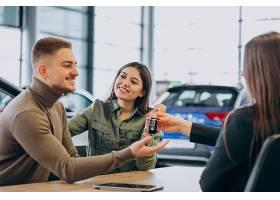 一对年轻夫妇在汽车展厅与销售人员交谈_7200773