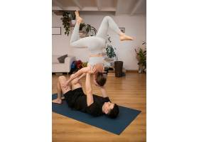 一对年轻夫妇在现代室内的家里一起练习瑜伽_13417859