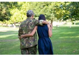 一对情侣在公园的草坪上拥抱并一起散步的背_11622122