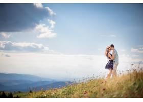 一对情侣站在青山上温柔地拥抱着绚丽的风景_1621693