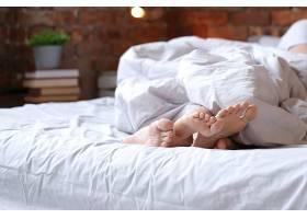 一对穿着双人睡衣躺在床上的夫妇可以看到_9108412