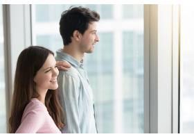 一男一女透过窗户看城市风景_3955536