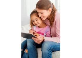 两姐妹在家一起使用平板电脑_13108787