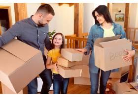 中等射程的父母和拿着盒子的孩子_12976376