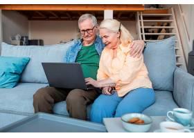 中景笑脸退休夫妇手持笔记本电脑_12892281