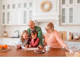 中等镜头的祖父母和女孩在厨房里_12975245