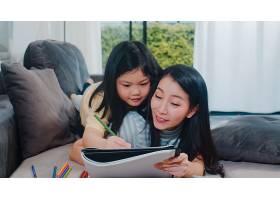 亚洲中年妇女在家教女儿做作业和画画生活_6142519
