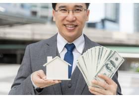 亚洲商人肖像手持现金美元钞票和商业区_11872307