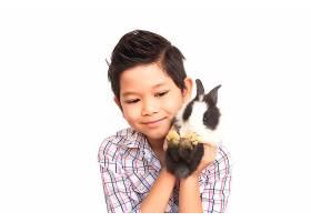 亚洲孩子与可爱的小兔子玩耍隔离在白色上_3805630