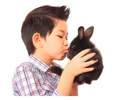 亚洲孩子与可爱的小兔子玩耍隔离在白色上_3805631