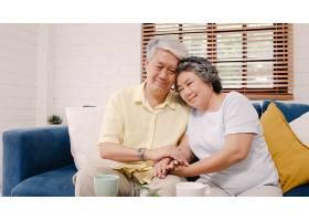 亚洲老年夫妇在客厅里手牵手幸福地躺在家_4396338