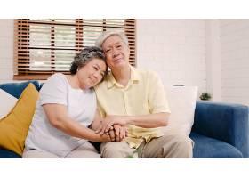亚洲老年夫妇在客厅里手牵手幸福地躺在家_4396339