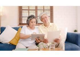 亚洲老年夫妇在家中用平板电脑在客厅看电视_4396327