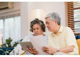 亚洲老年夫妇在家中用平板电脑在客厅看电视_4396366