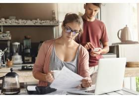 面临经济困难的年轻家庭戴眼镜的妇女在用_9532830