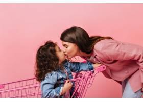 高兴的年轻女子亲吻卷曲的女儿坐在购物车_12432012