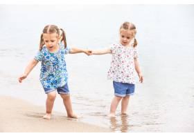 海边的孩子们沿着海水走的双胞胎_8264582