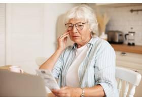 灰发苍苍的女养老金领取者戴着眼镜拿着笔_11200030