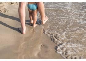 父子俩在海滩上散步的中景_4937565